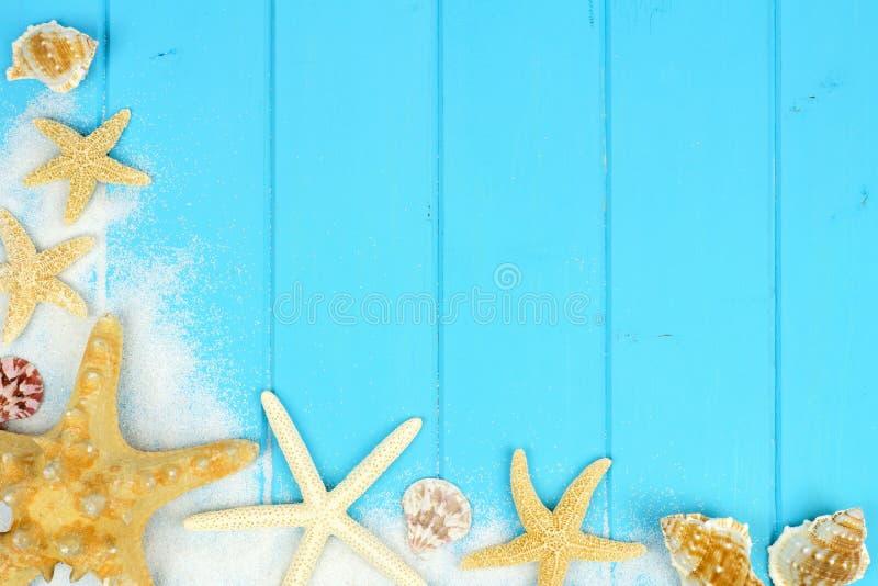 Hoekgrens van zand, zeeschelpen en zeester op blauw hout royalty-vrije stock foto's