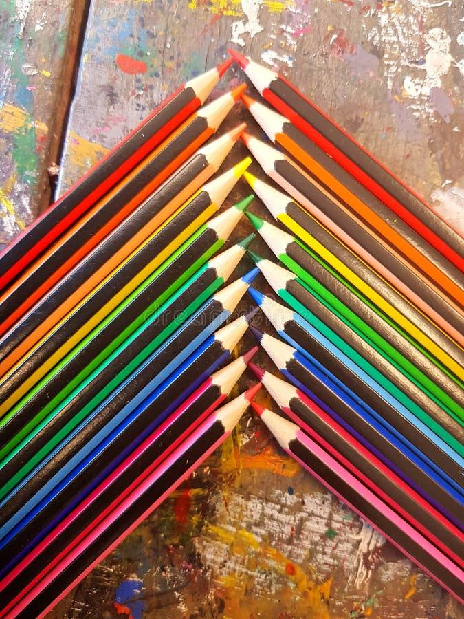 Hoekige die mening van potloden in regenboogorde wordt opgemaakt op een lijst met een witte achtergrond stock afbeelding
