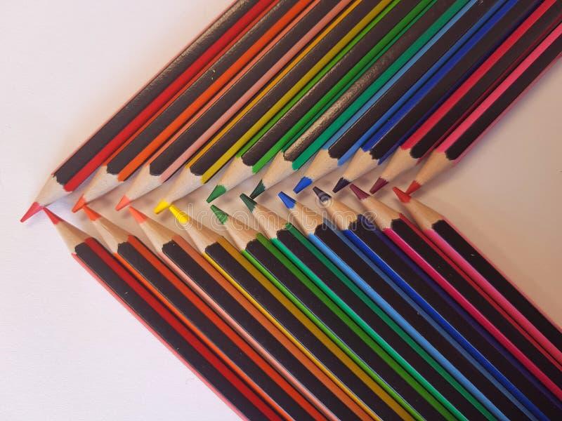 Hoekige die mening van potloden in regenboogorde wordt opgemaakt op een lijst met een witte achtergrond royalty-vrije stock fotografie
