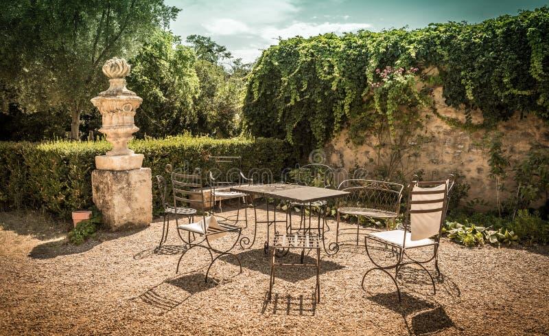 Hoekje van de de zomer het vreedzame uitstekende tuin met metaalmeubilair royalty-vrije stock fotografie