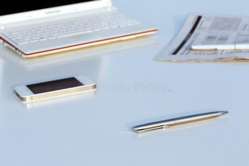 Hoekmening van het Werkplaats met Laptop Pen en Krant stock fotografie