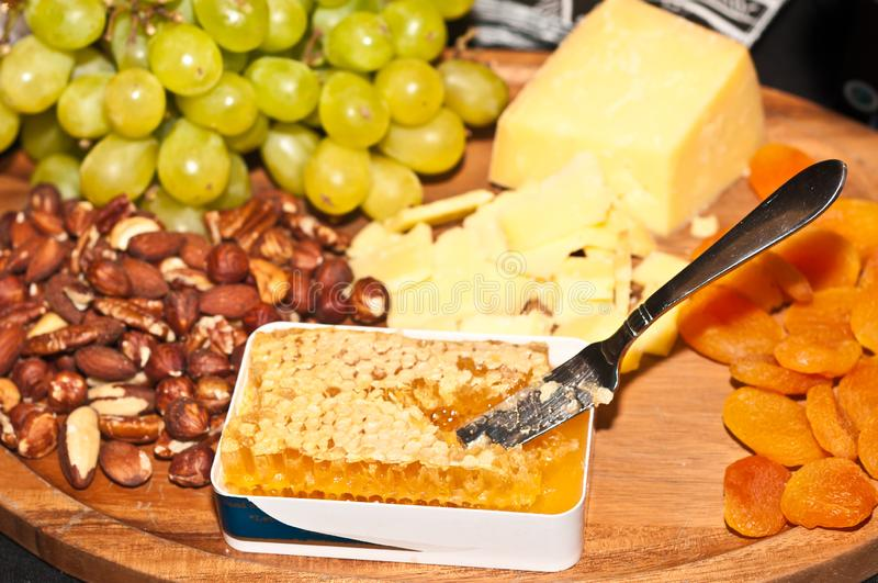 Hoeny comb, knife  on a rare wood platter with apricots, green grapes, a pile of hazelnuts and a wedge of cheddar cheese stock image
