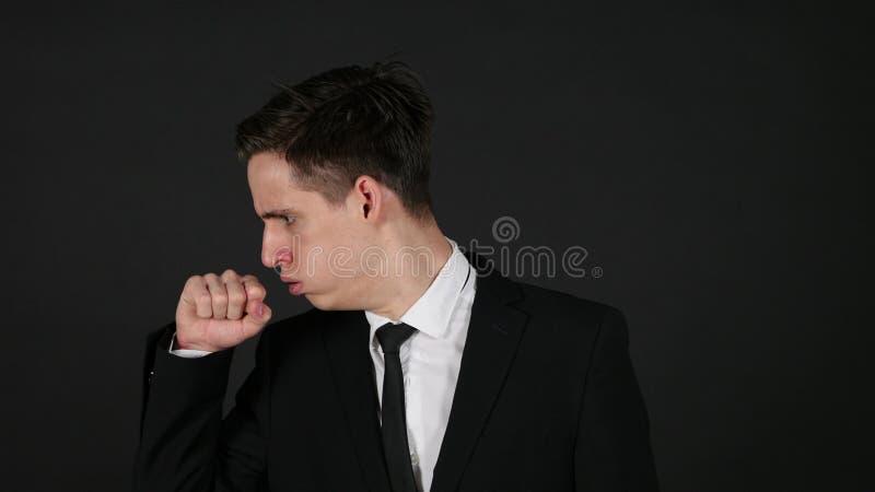 Hoest, hoestende zakenman, donkere zwarte achtergrond stock foto's