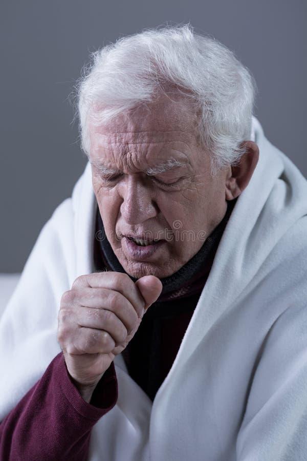 Hoestende mens omvat met deken royalty-vrije stock afbeelding