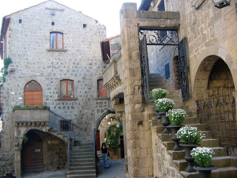 Hof der mittelalterlichen Stadt von Viterbo mit einigen Treppenhäusern mit Vasen weißen Blumen Italien lizenzfreie stockbilder
