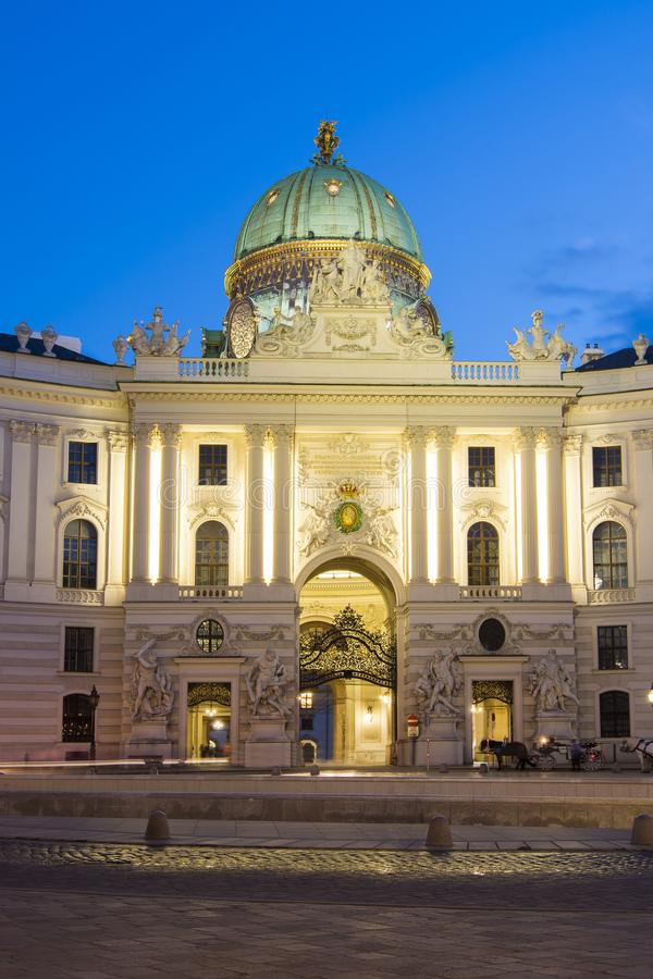 Hofburg在圣迈克尔广场Michaelerplatz的宫殿门面在晚上,维也纳,奥地利 免版税库存照片