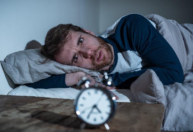 Hoffnungslose betonte junger Mann Whitschlaflosigkeit, die im Bett anstarrt entlang des Weckers versucht zu schlafen liegt stockbild