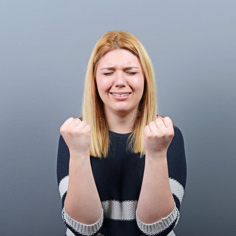 Hoffnungslose Frau, die um Gnade gegen grauen Hintergrund bittet stockfoto