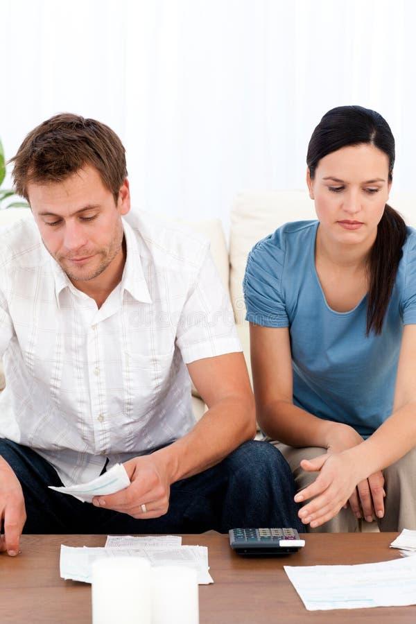 Hoffnungslose Paare, die ihre Rechnungen betrachten stockfotografie