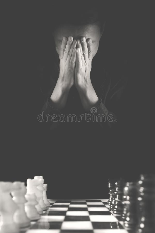 Hoffnungslose Person hat falsches und ist wahrscheinlich, das Schachspiel zu verlieren stockfotografie