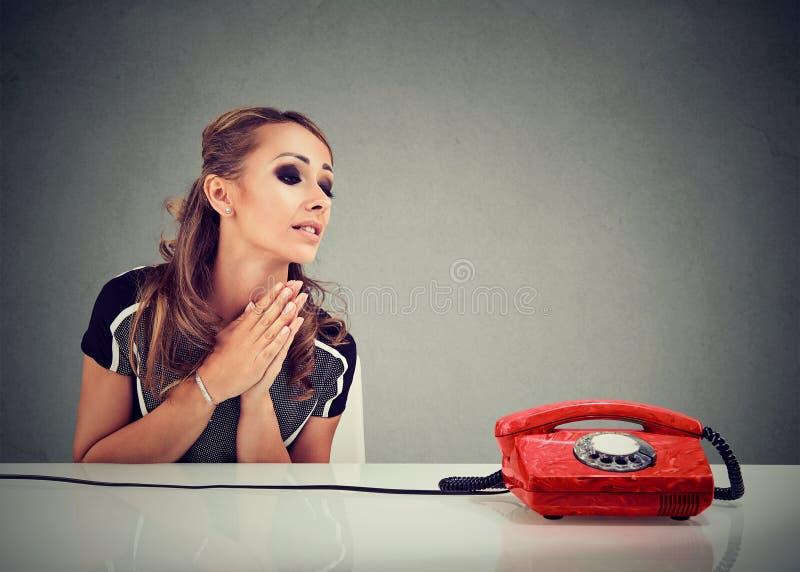 Hoffnungslose traurige Frau, die auf jemand wartet, um sie anzurufen lizenzfreies stockbild