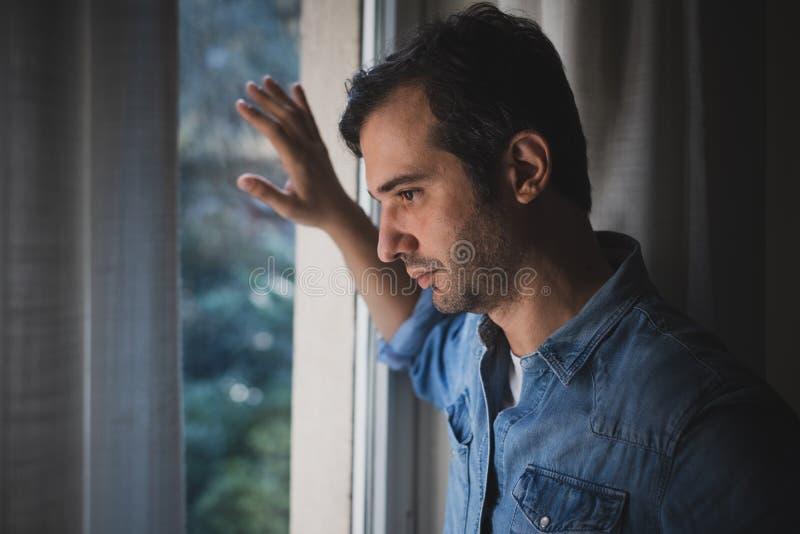Hoffnungsloses Manngefühl allein und verloren, Fenster heraus schauend stockfotos
