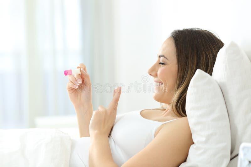 Hoffnungsvolle Frau, die zu Hause Schwangerschaftstest überprüft stockfoto