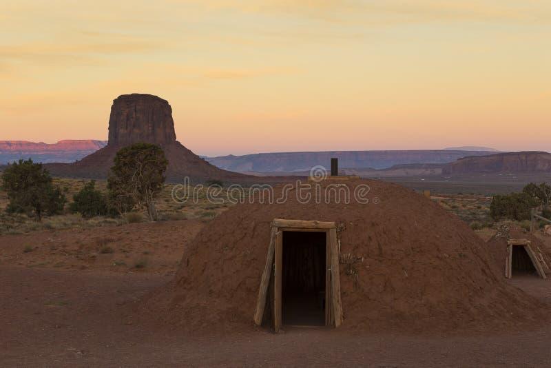 Hogan de Navajo au lever de soleil avec une butte à l'arrière-plan images libres de droits