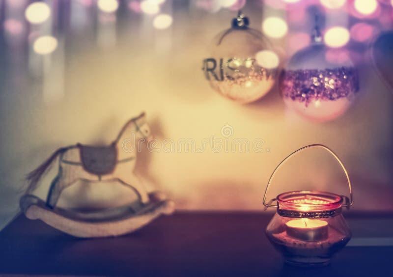 Hogar acogedor de la Navidad con la decoración, la vela, el caballo mecedora y el bokeh festivos foto de archivo