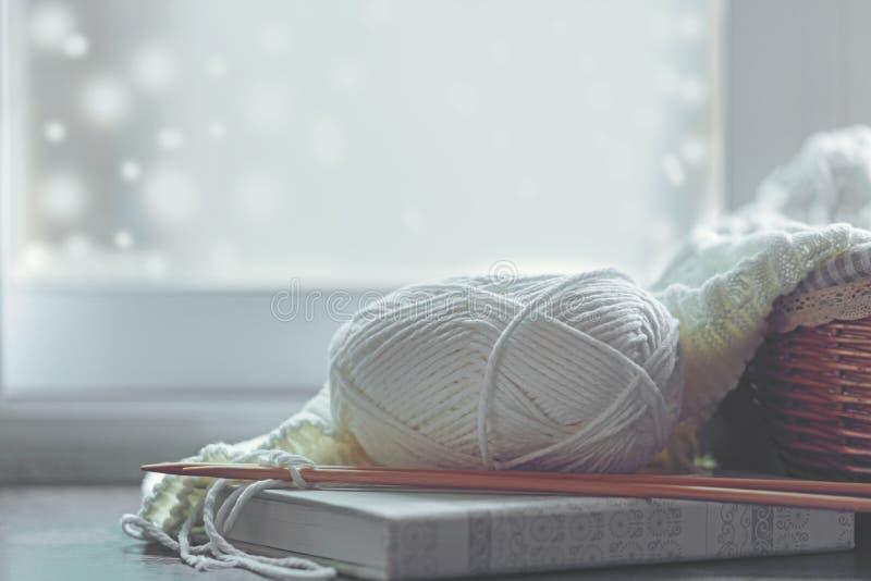Hogar acogedor del invierno con los suéteres y la bola hechos punto calientes del hilado cerca del alféizar, aficiones caseras, t imágenes de archivo libres de regalías
