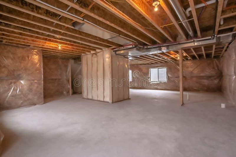 Hogar bajo construcción con los haces que enmarcan interiores y la pared cubierta plástica fotografía de archivo
