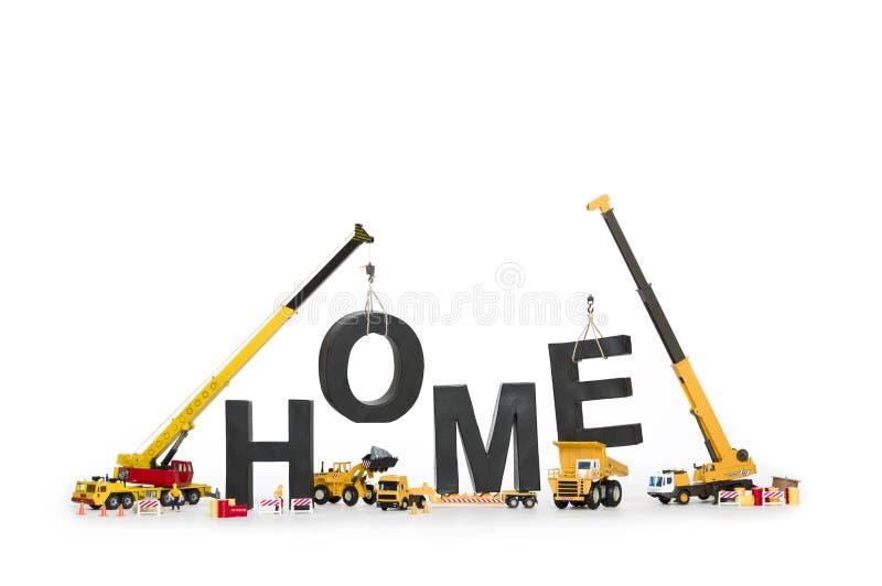 Hogar bajo construcción: Máquinas que crean hogar-palabra. fotos de archivo