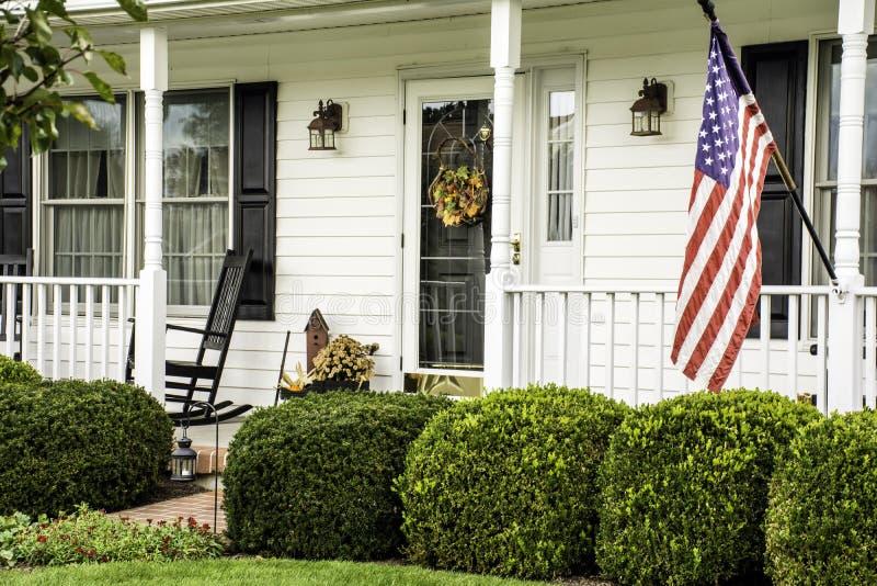 Hogar colonial blanco con la bandera americana foto de archivo