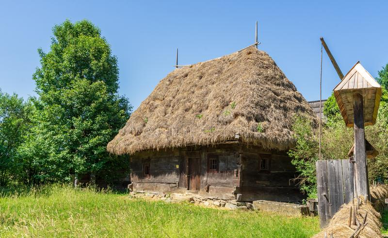 Hogar con el tejado de la paja en un pueblo tradicional en Sighet foto de archivo