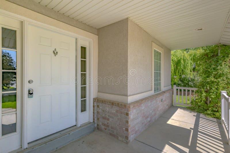 Hogar con la puerta principal blanca y el pórtico iluminado por el sol imagen de archivo
