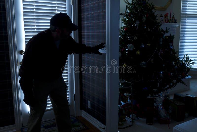 Hogar de Breaking In To del ladrón en la Navidad con B imagen de archivo