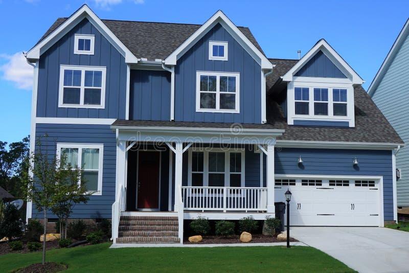 Hogar de dos pisos, azul, suburbano en una vecindad en Carolina del Norte imagen de archivo
