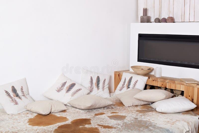 Hogar de la comodidad interior escandinavo con las almohadas Interior moderno de la casa de campo con la cama de madera, leña, ch imagenes de archivo