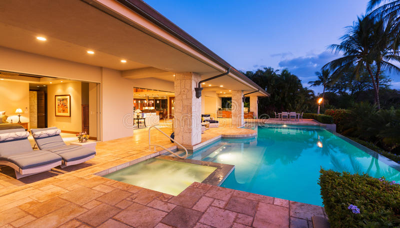 Hogar de lujo con la piscina en la puesta del sol fotos de archivo