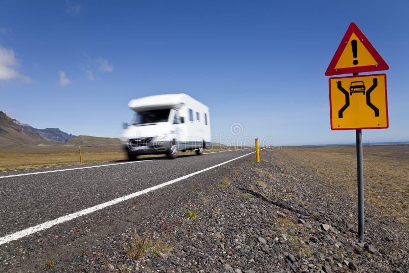Hogar de motor que conduce en el camino con la muestra del peligro imagen de archivo