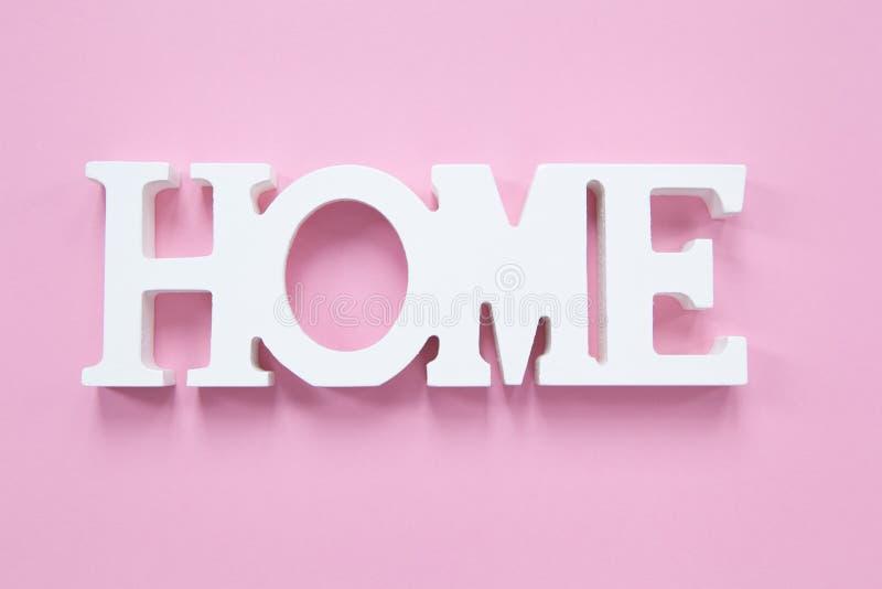 Hogar decorativo de la palabra en un fondo rosado milenario Concepto de comodidad casera, romance Formato horizontal fotos de archivo