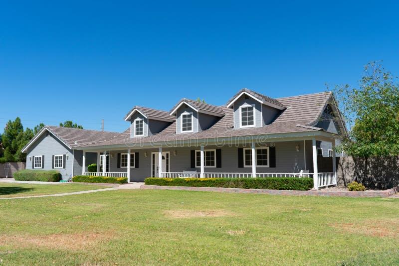 Hogar del estilo del rancho con el pórtico y las ventanas abuhardilladas foto de archivo libre de regalías