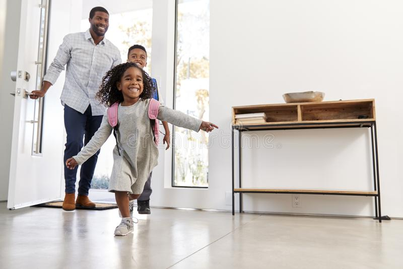 Hogar del hijo y de la hija de Collecting And Bringing del padre después de la escuela imagen de archivo libre de regalías