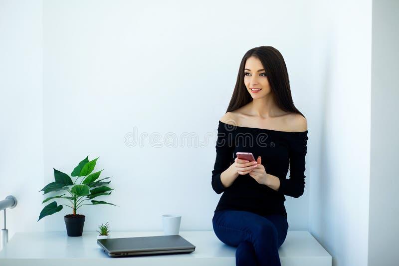 Hogar del negocio Trabajo en casa La mujer joven hermosa trabaja en el ordenador Vestido en chaqueta y tejanos negros E foto de archivo