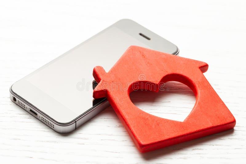Hogar elegante que corre del teléfono Casa y smartphone de madera en la tabla de madera blanca imagen de archivo