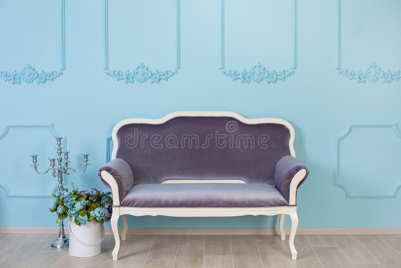 Hogar elegante retro acogedor con la decoración inspirada por los diseñadores y el alma del florista con colores reales silla vie fotografía de archivo libre de regalías