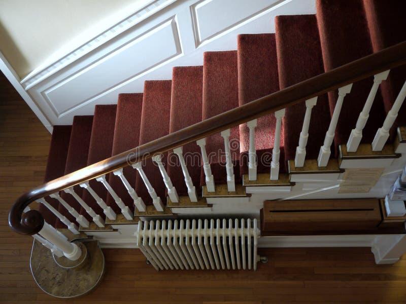Hogar: escalera sunlit con la alfombra roja foto de archivo
