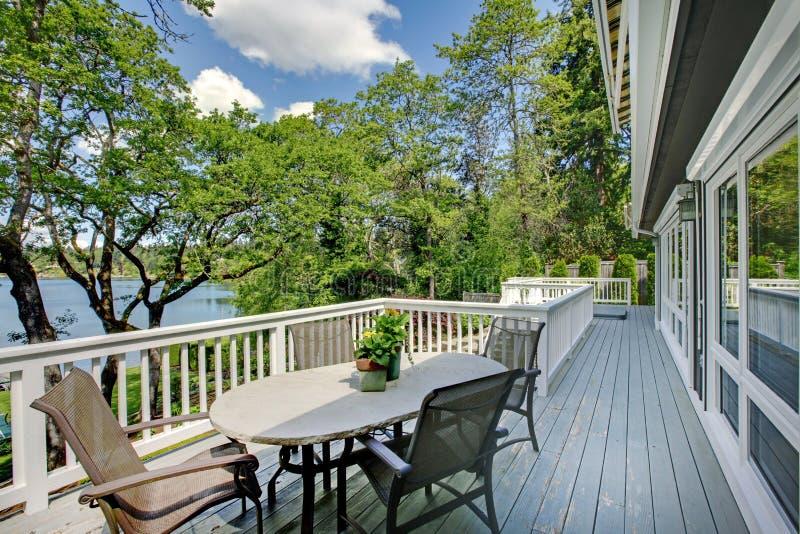 Hogar largo grande del balcón exterior con la tabla y las sillas, opinión del lago. foto de archivo libre de regalías