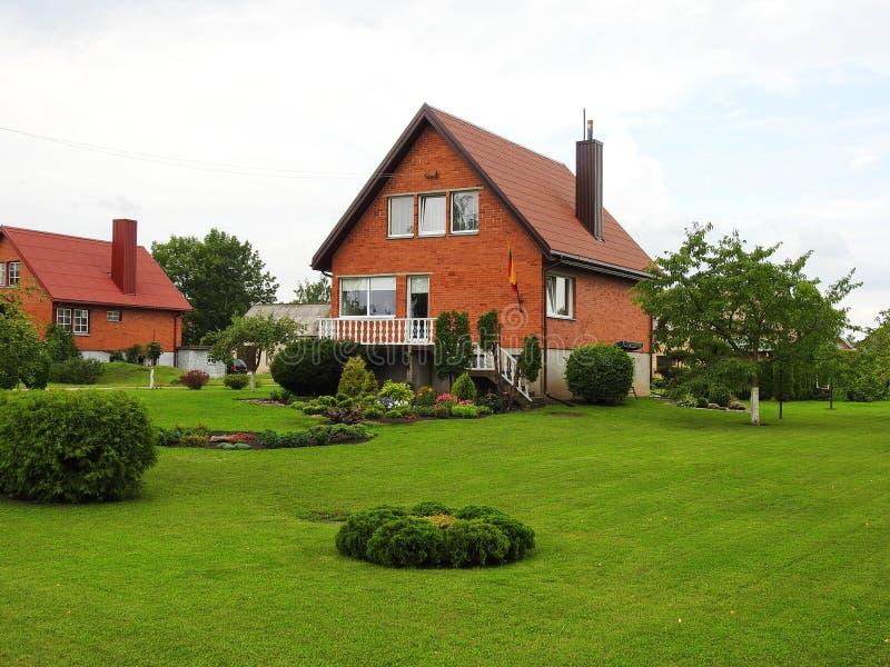 Hogar rojo hermoso y jardín agradable, Lituania foto de archivo