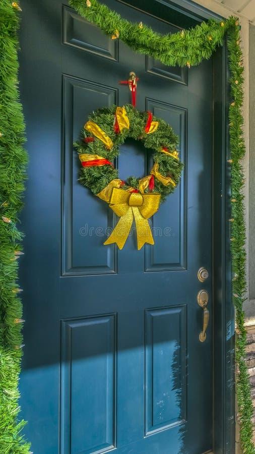 Hogar vertical claro con un pórtico y una puerta principal iluminados por el sol adornados con la guirnalda y la guirnalda foto de archivo libre de regalías
