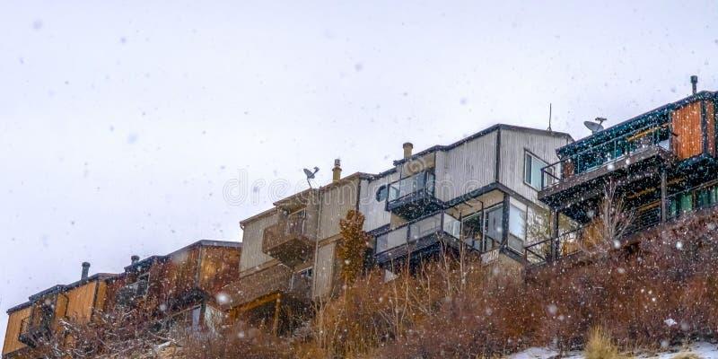 Hogares claros del panorama en la montaña nevosa contra el cielo brillante imagen de archivo libre de regalías