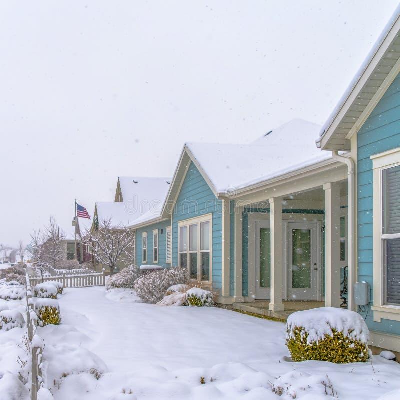 Hogares con los tejados nevados y yardas en invierno fotografía de archivo libre de regalías