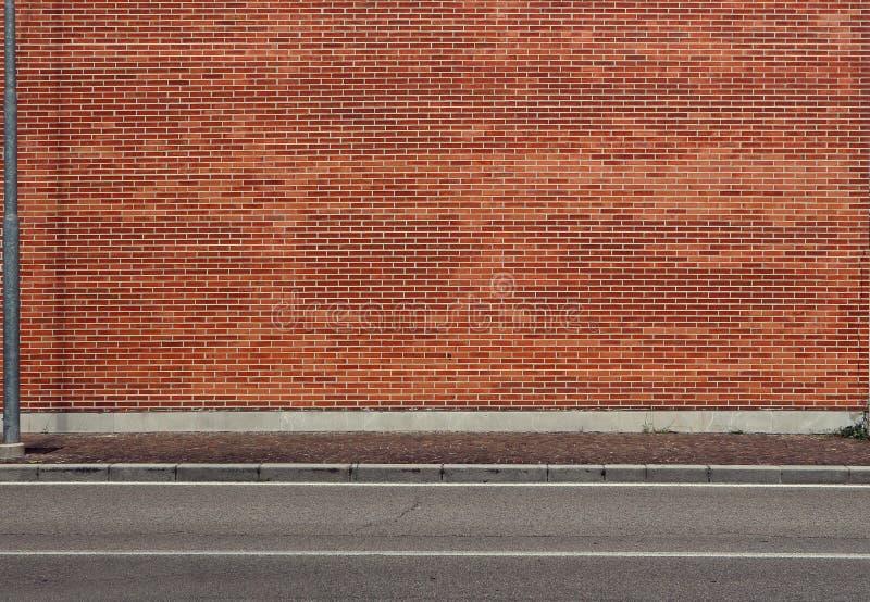 Hoge bakstenen muur met een porfierstoep en een asfaltstraat vooraan Stedelijke Achtergrond stock foto's
