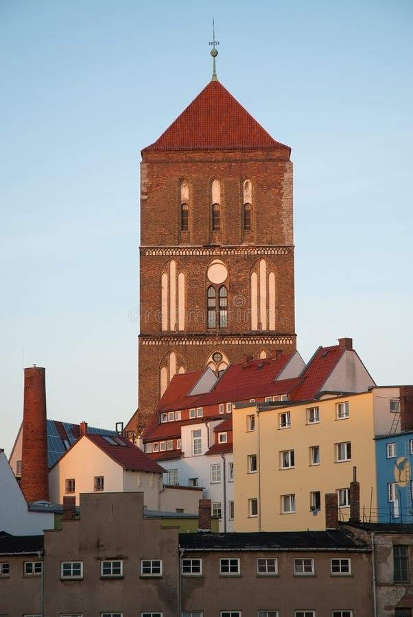 Hoge die kerktoren achter huizen wordt gezien stock afbeeldingen