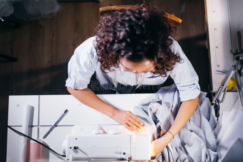 Hoge die mening van naaisterzitting voor naaimachine en het werken wordt geschoten stock fotografie