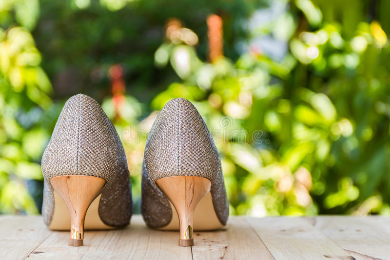 Hoge hiel van gouden schoenen op hout stock foto's