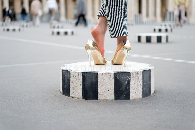 Hoge hielschoenen op vrouwelijke voeten op stadsvierkant Benen in glamour gouden schoenen Parijs, Frankrijk Manierschoenen op kol stock foto's
