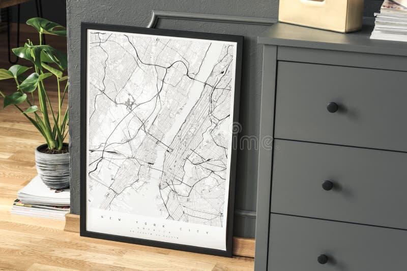 Hoge hoek op witte affiche op houten vloer tussen installatie en grijs kabinet in het binnenland Echte foto royalty-vrije stock afbeelding