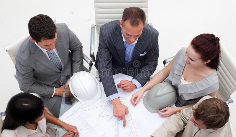 Hoge hoek van jonge architecten die met plannen werken stock afbeeldingen