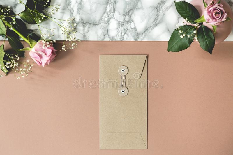Hoge hoek van vuil roze en marmeren bureau met verse rozen, document envelop en lege ruimten voor uw notitieboekjes en pennen stock foto's